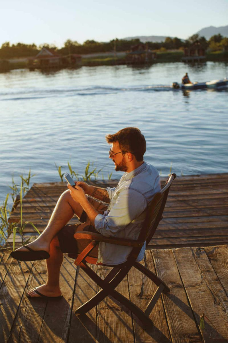 Mann entspannt sich im Urlaub - und steuert mit Smart-Home seine Rolläden und Lampen zu Hause