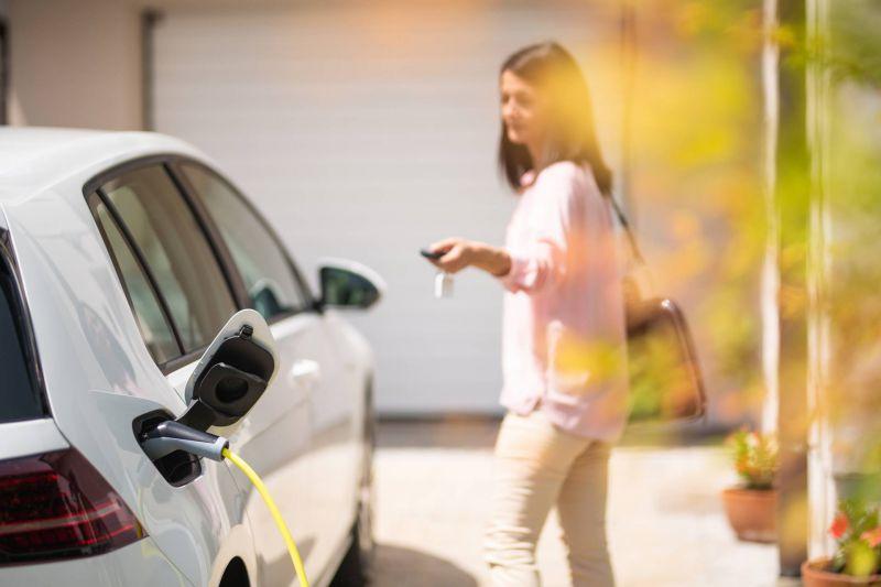 Frau lädt E-Auto zu Hause