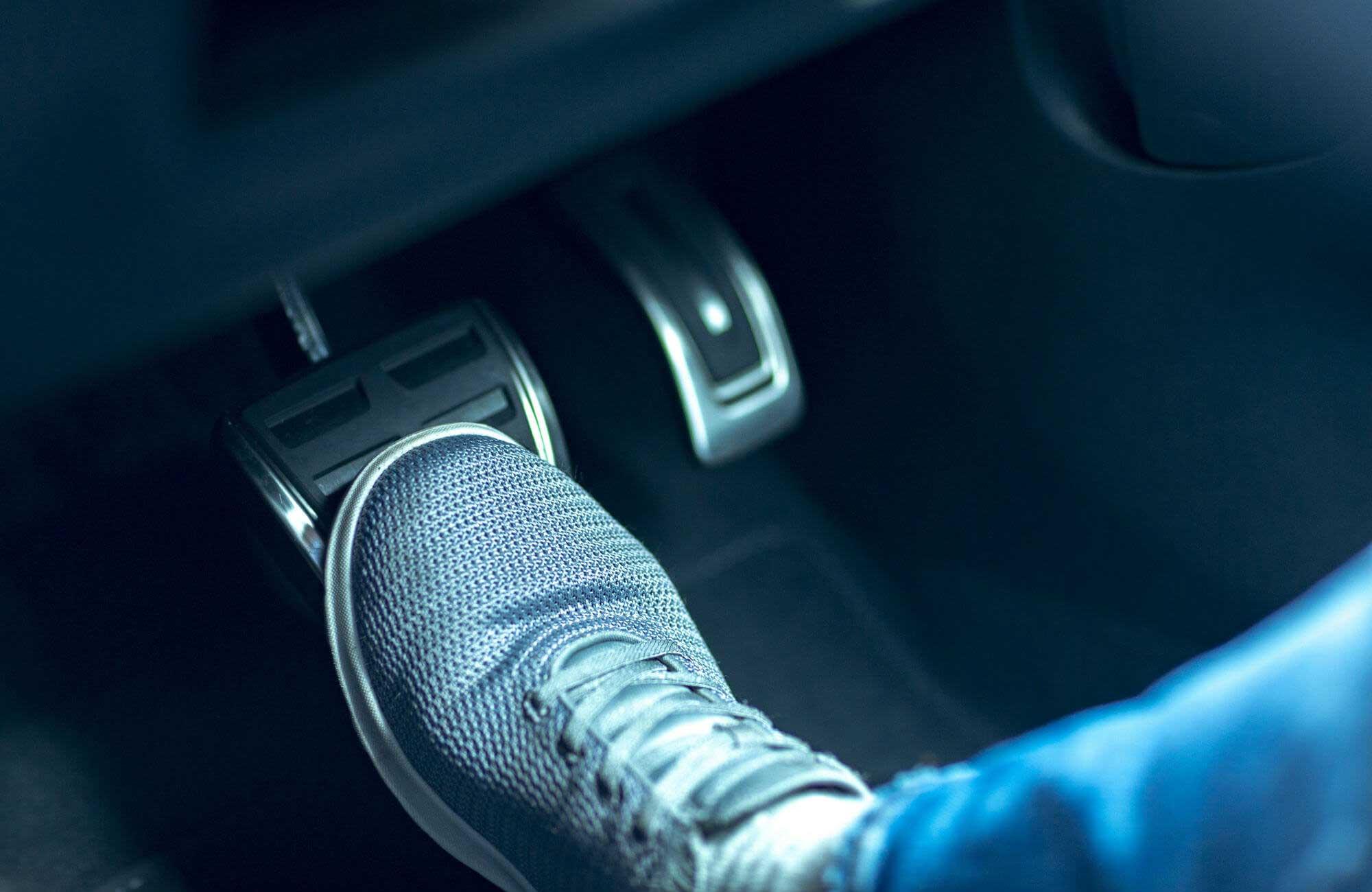 Fuß steht auf dem Bremspedal eines Autos.