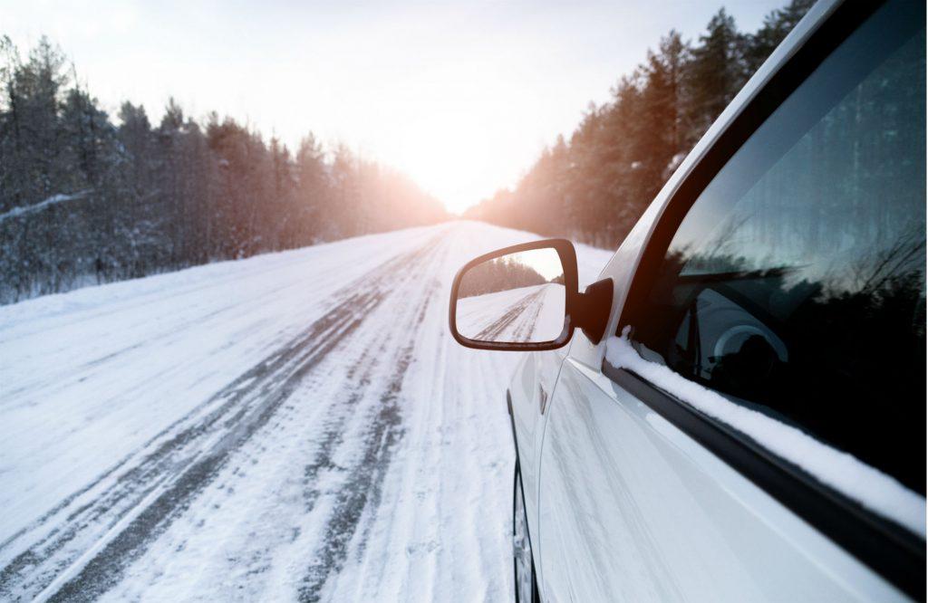 E-Auto fährt auf einer schneebedeckten Straße.