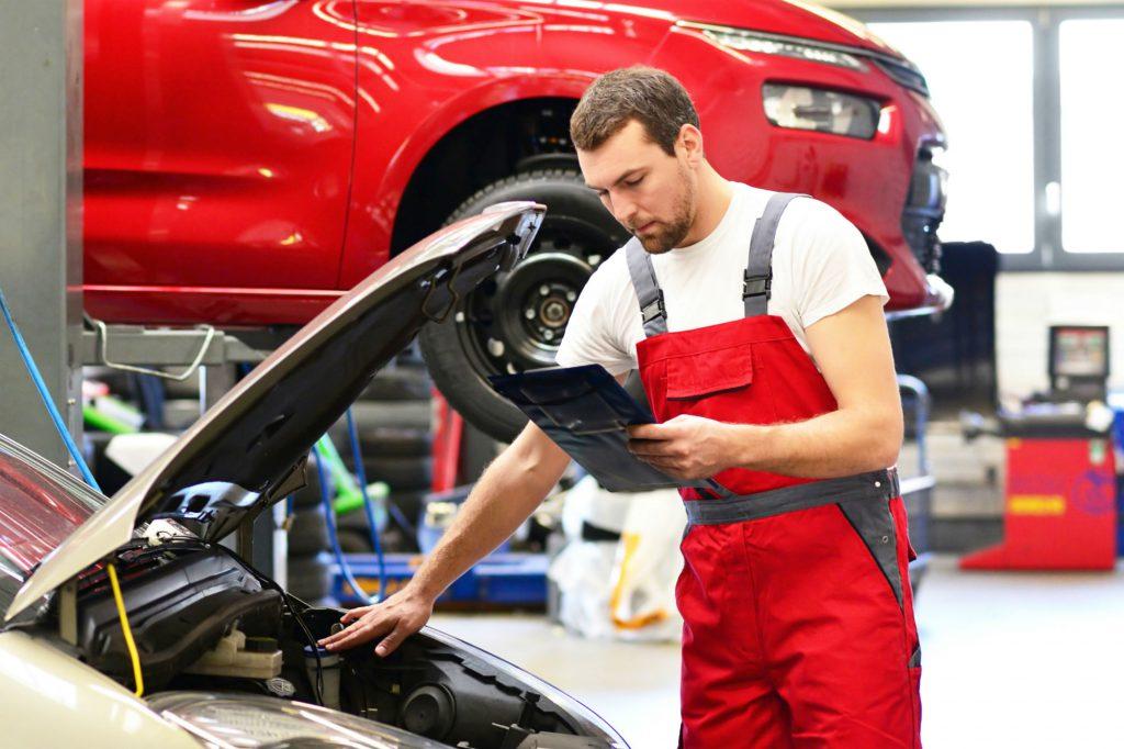 Kfz-Mechaniker schaut in der Werkstatt unter die Motorhaube eines Autos.