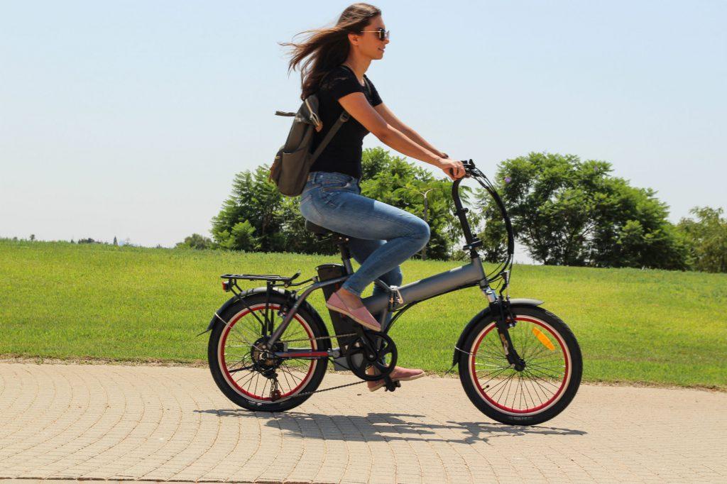 Frau fährt auf einem kompakten E-Bike durch einen Park.