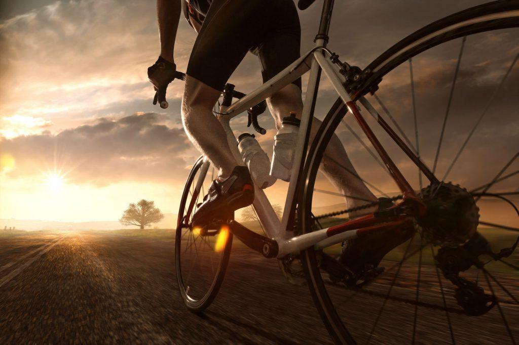 Rennradfahrer fährt in den Sonnenuntergang.
