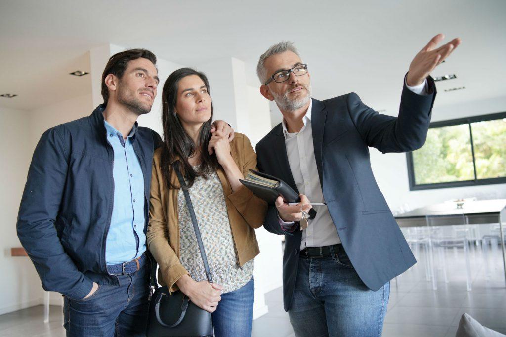 Makler führt Pärchen durch die Immobilie