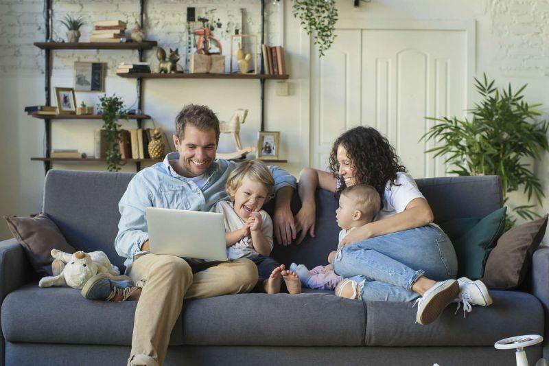 Vierköpfige Familie sitzt mit Laptop auf einer Couch