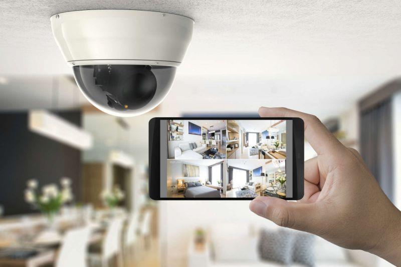 Hand hält Smartphone vor einer Überwachungskamera