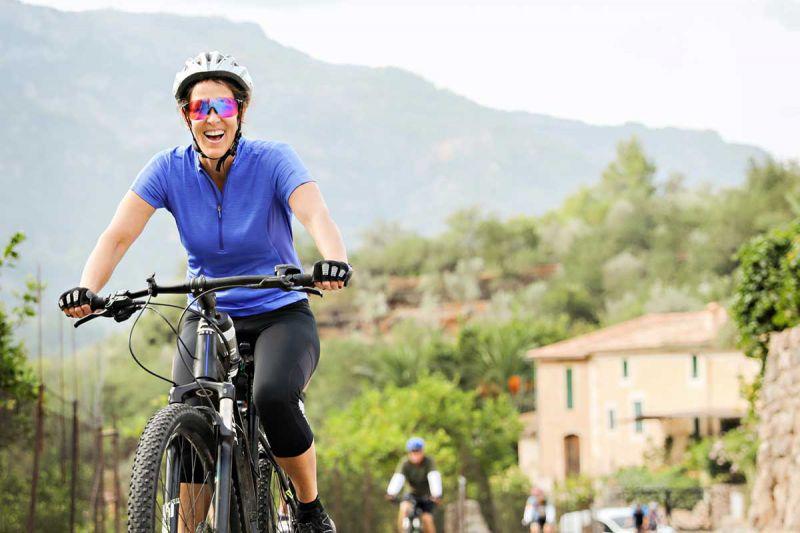 Frau fährt dem E-Bike durchs Gelände