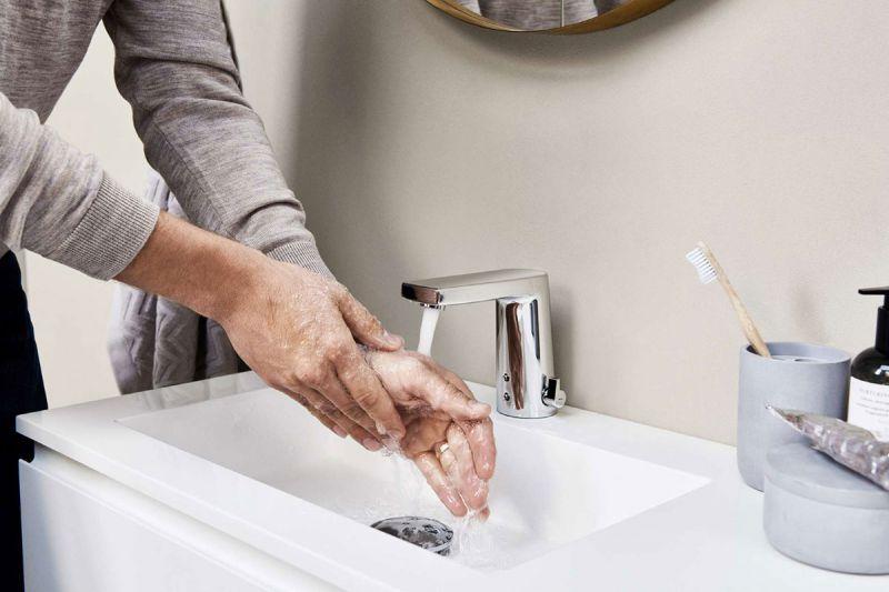 Hände was an einem smarten Wasserhahn