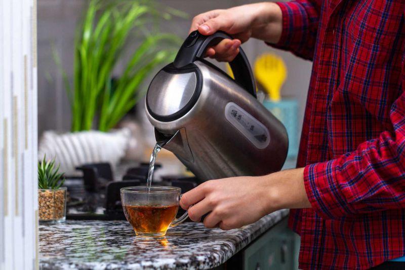 Wasser in ein Teeglas einschenken mit dem Wasserkocher.