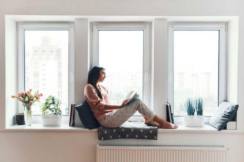 Frau entspannt am Fenster