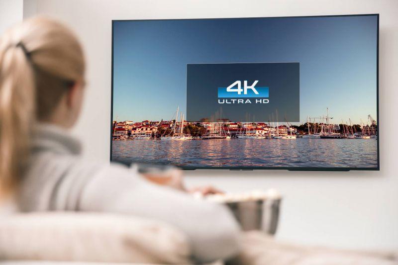 Frau schaut 4K fernsehen