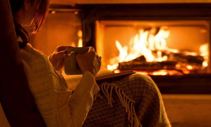 Frau mit Decke und Tee vor dem Kaminofen eingekuschelt