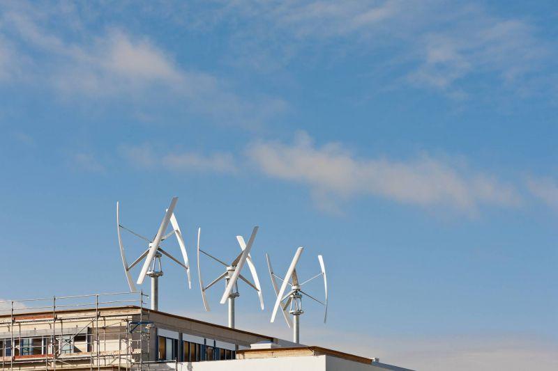 Drei vertikale Windkraftanlagen auf einem Dach