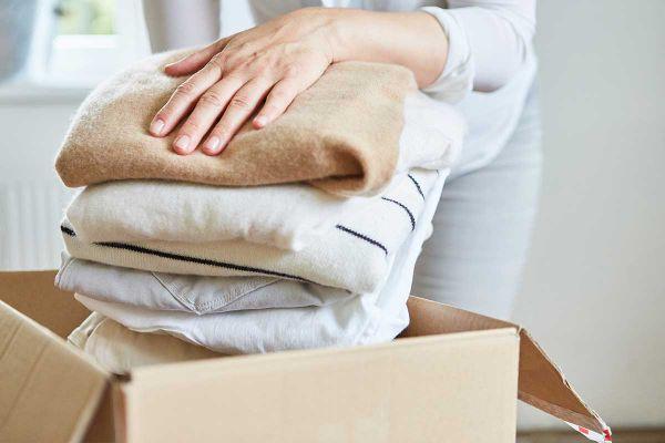 Frau packt Klamotten in Karton