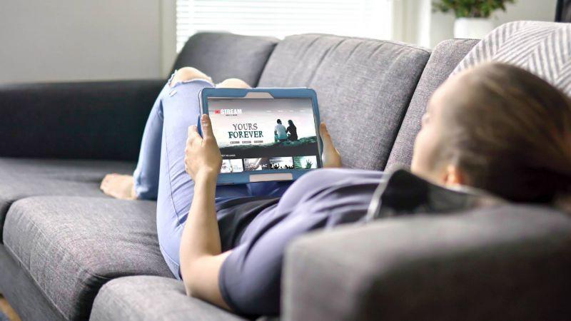 Frau streamt Film am Tablet und liegt dabei auf der Couch