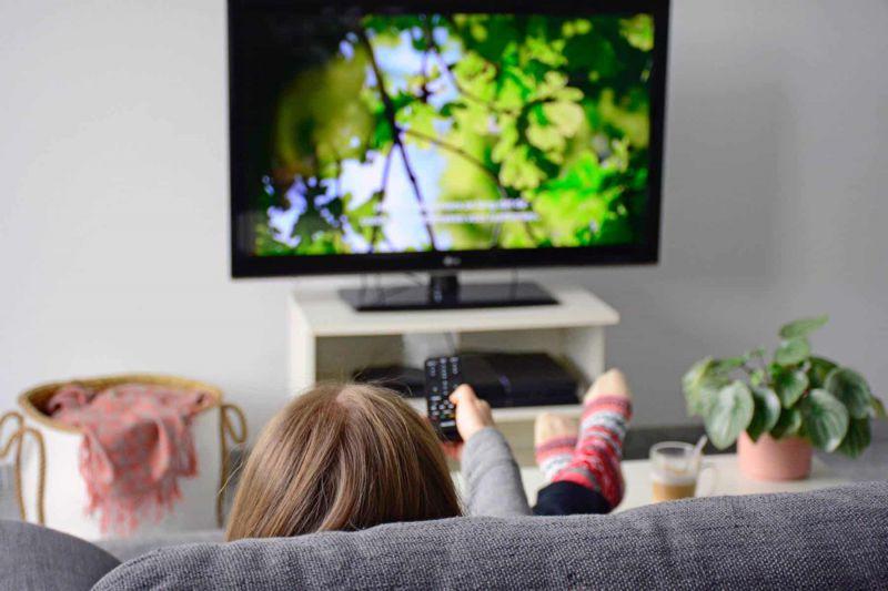 Junge Frau schaut Fernsehen und sitzt auf einem grauen Sofa